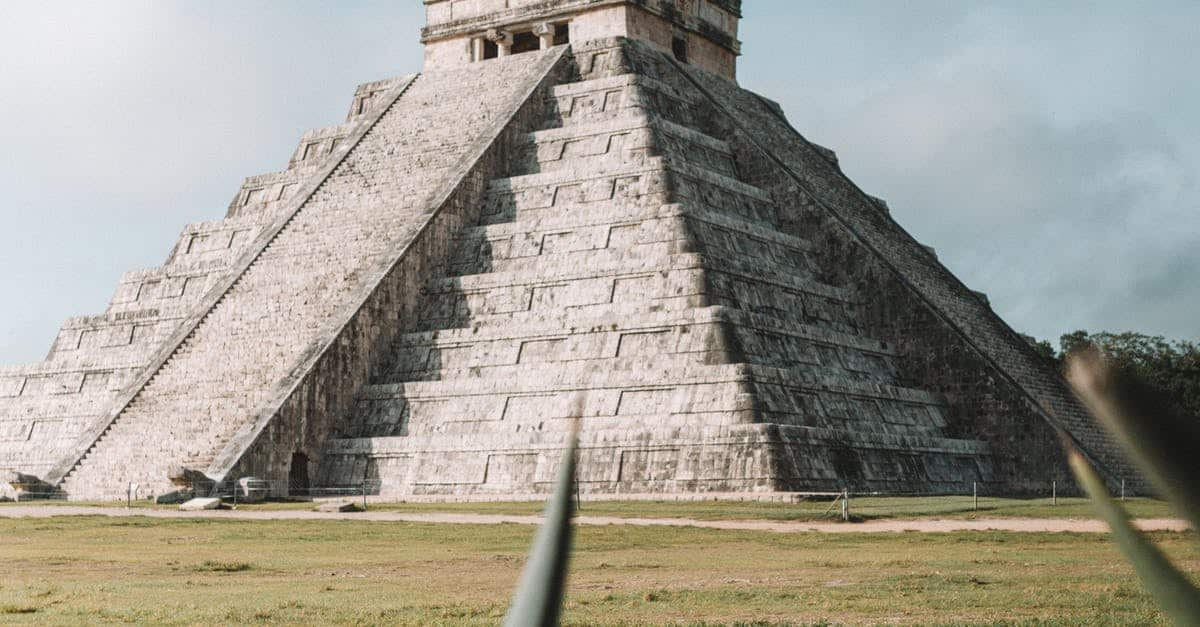 A large stone building with Chichen Itza in the background